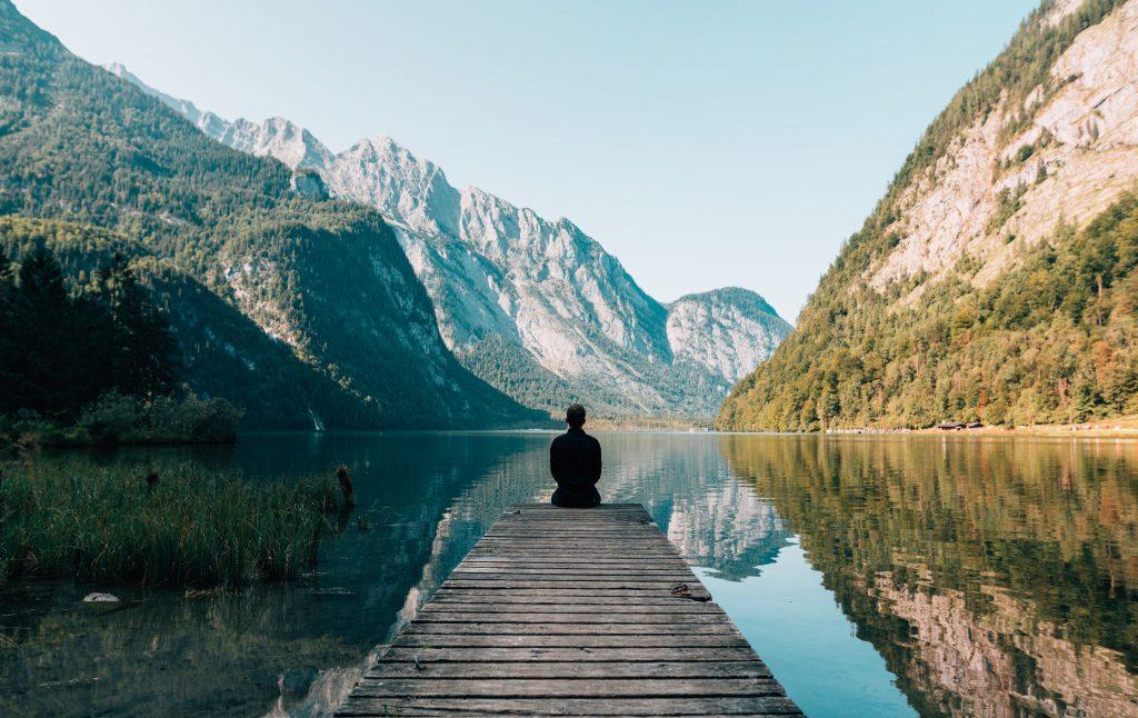 Man looking at lake and mountains
